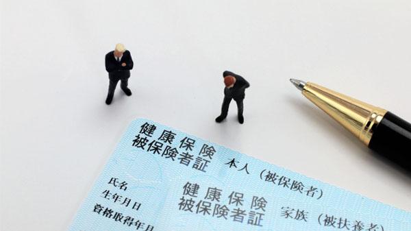 保険証とペン・二人のサラリーマンの人形