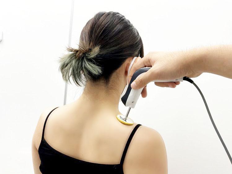 肩にハイボルト治療を受けている後ろ姿の女性