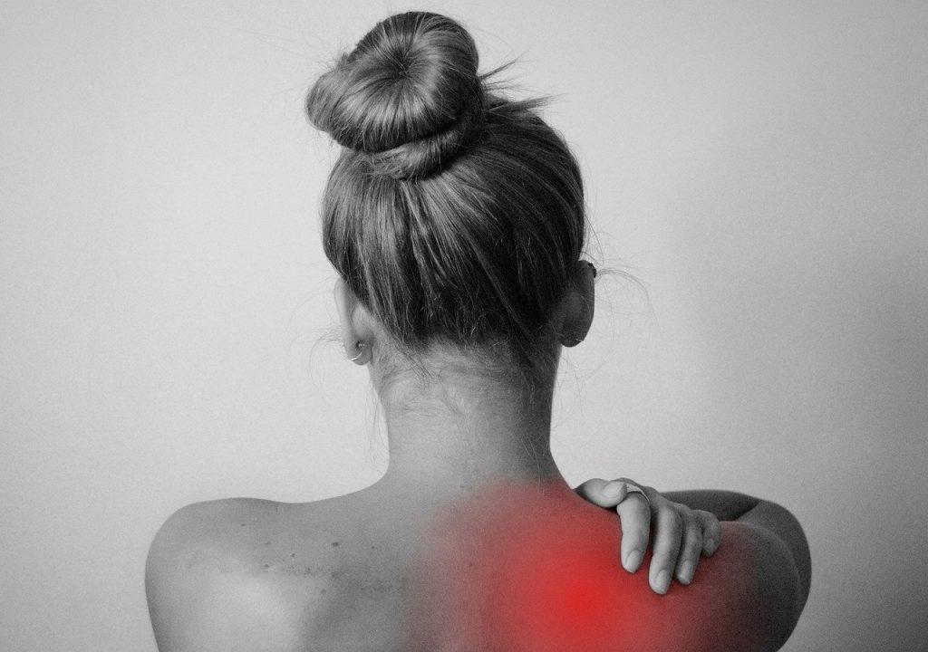 右肩に痛みがあり左手で痛みを押えている女性の後ろ姿